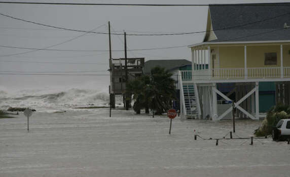 Waves and rising water were already threatening Surfside Beach by Friday morning. Photo: Julio Cortez, Chronicle