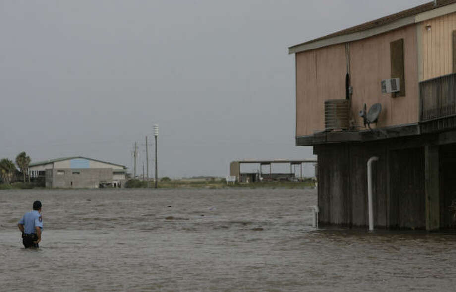 Surfside Beach Police Chief Randy Smith wades through rising waters Friday to ask holdouts to leave before Hurricane Ike's arrival. Photo: Julio Cortez, Chronicle