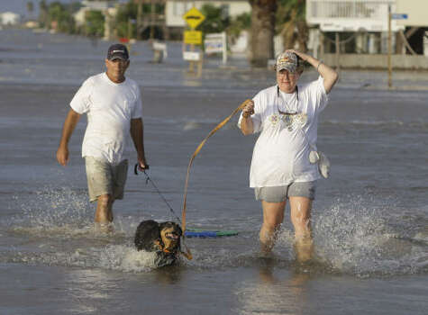 Max and Diane Hall take their dog Sissy with them as they leave Surfside Beach. Photo: Eric Gay, AP