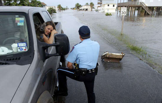 Surfside Beach Police Chief Randy Smith talks with Elizabeth Taylor on her way out of town. Taylor 's husband planned to remain behind. Photo: Eric Gay, AP