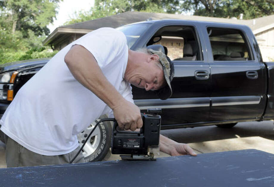 Brad Stafford makes the final cuts to a piece of board to cover a window on his Houston house as Hurricane Ike approached Friday. Photo: Pat Sullivan, AP
