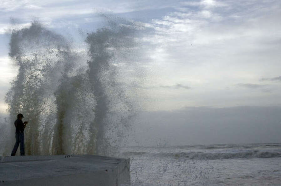 Daniel Gallegos, 26, of Galveston enjoys the waves braking over the seawall Friday. Gallegos planned