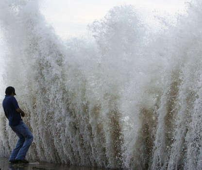 Daniel Gallegos shrinks as a big wave crashes into the seawall. Photo: Matt Slocum, AP