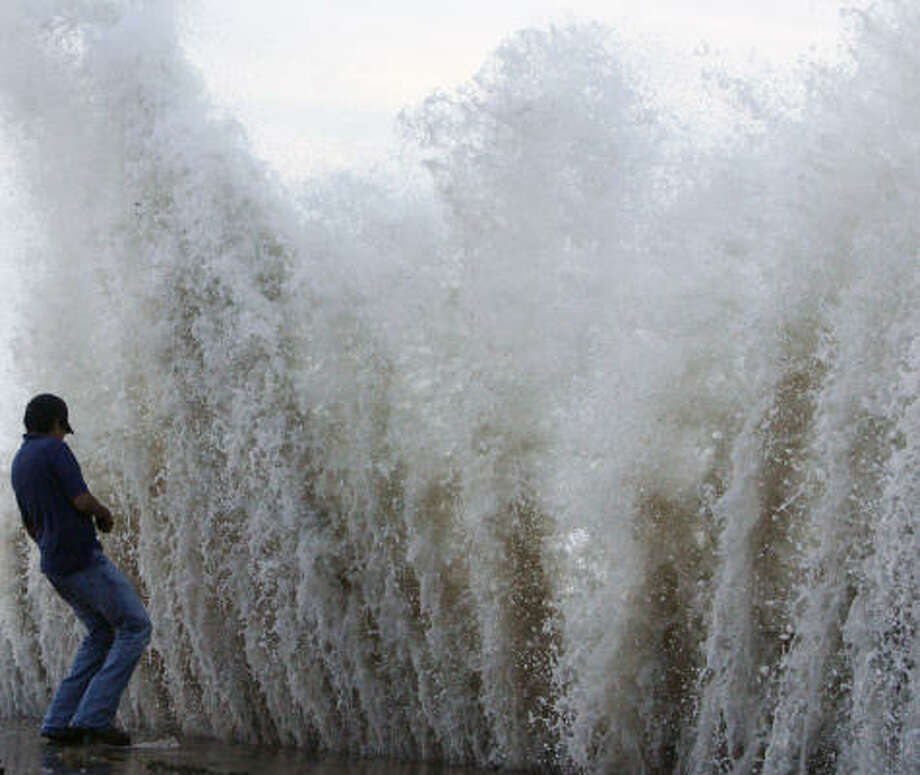 Daniel Gallegos shrinks as a big wave crashes into the seawall. Photo: Matt Slocum, AP