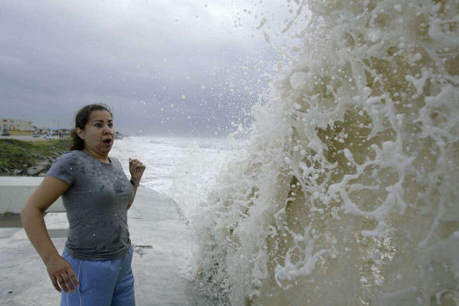 Sylvia Renteria of Houston reacts to a big wave crashing into Galveston's sea wall Friday. Photo: Matt Slocum, AP