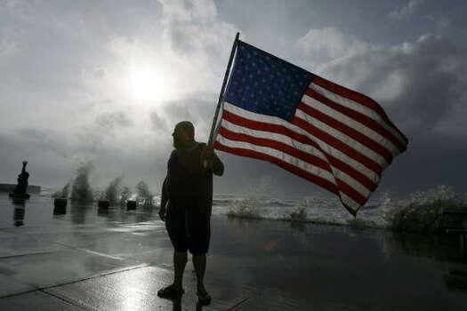 Robert Shumake brought along a flag for his stroll along Galveston's seawall Friday. Photo: Matt Slocum, AP