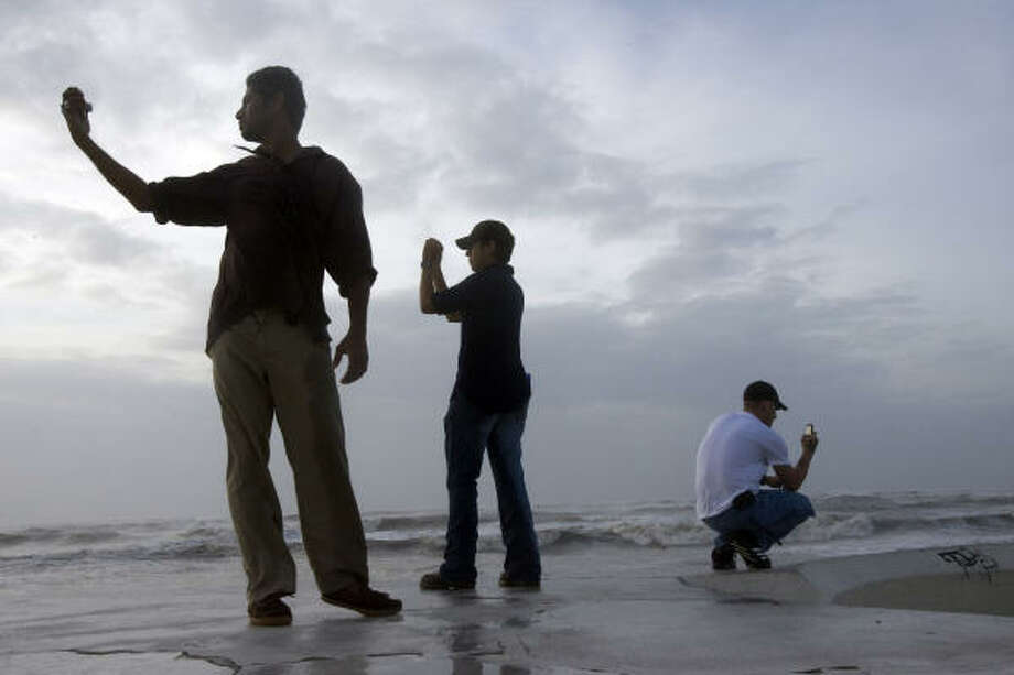 Manteen Ali, 24, of Houston, Daniel Gallegos, 26, of Galveston, and Justin Hoyt, 26, of Houston get the last pictures of open sky on Galveston's seawall as clouds from Hurricane Ike began to arrive Friday. Photo: Johnny Hanson, Chronicle