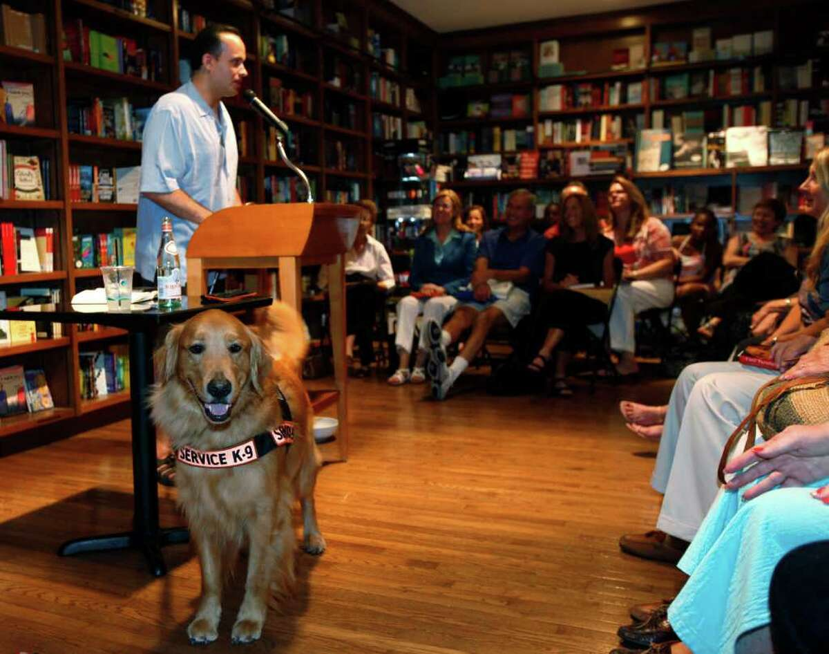"""In this June 28, 2011 photo, former U.S. Army Captain Luis Carlos Montalvan speaks as his service dog """"Tuesday"""" looks on at a book signing for his book """"Until Tuesday,"""" at a book store in Coral Gables, Fla. Since serving two tours of duty, for which he received two Bronze Stars and the Purple Heart, the former Army captain has become a strong critic of the war and an advocate for better care of those who served. (AP Photo/Wilfredo Lee)"""