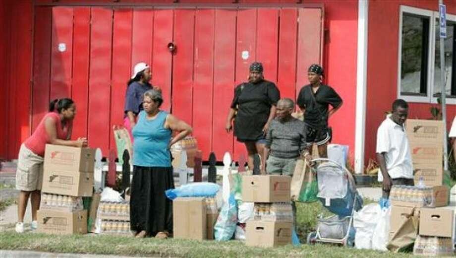 Varias personas aguardan a ser transportadas tras recibir alimentos y otros suministros en un centro de distribución de ayuda en la Universidad de Houston, debido al huracán Ike, el jueves, 18 de septiembre del 2008. Photo: Marcio Jose Sanchez, AP