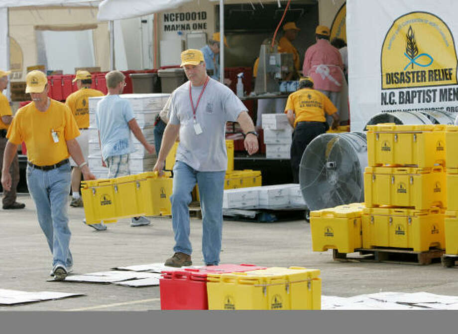 Members of North Carolina Baptist Men carry containers full of hot food to Red Cross vans headed to Baytown. Photo: Marcio Jose Sanchez, AP