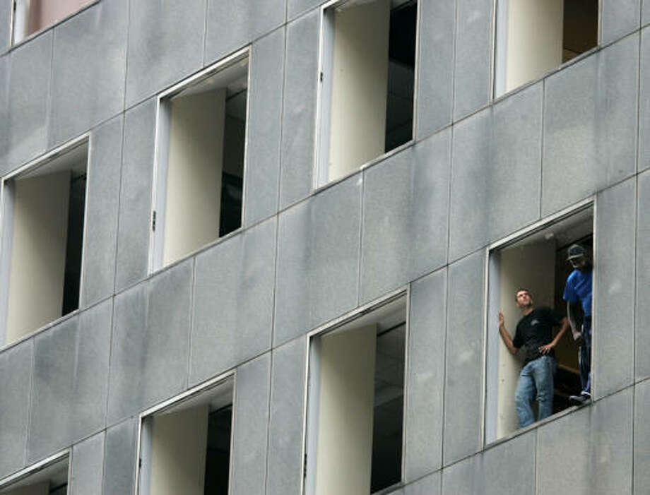 Workers look out the shattered windows of the JP Morgan Chase Tower in downtown Houston, Texas, Sunday. Photo: Marcio Jose Sanchez, AP