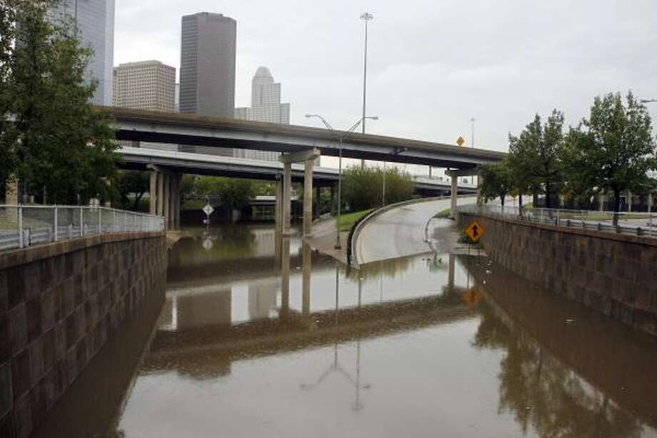 Heavy flood waters submerge a highway access ramp to I-45 near downtown Houston on Sunday. Photo: G.J. McCarthy, AP