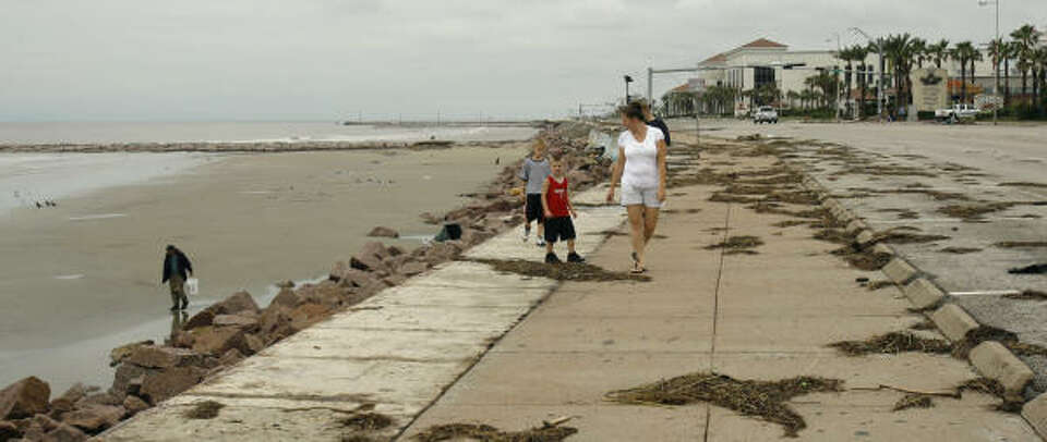 People walk on the sea wall, right, as another walks on the beach Sunday in Galveston, Texas. Hurric