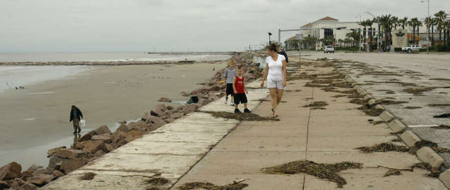 People walk on the sea wall, right, as another walks on the beach Sunday in Galveston, Texas. Hurricane Ike blasted ashore early Saturday. Photo: Harry Cabluck, AP