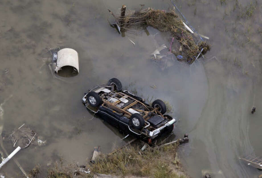 An overturned car sits in floodwaters from Hurricane Ike Sunday in Gilchrist, Texas. Photo: David J. Phillip, AP