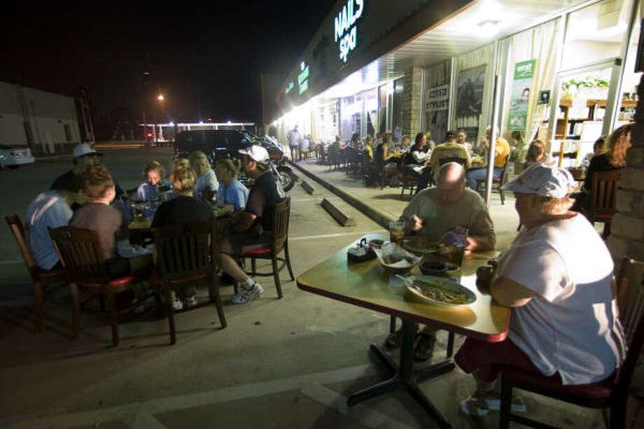 Clientes del restaurante de comida mexicana Mario's comen en mesas improvisadas en el estacionamiento. El negocio, en la autopista I-45 Norte y Rayford Road, en Spring, abrió pese a no contar con suministro de energía eléctrica. Photo: Brett Coomer, Houston Chronicle