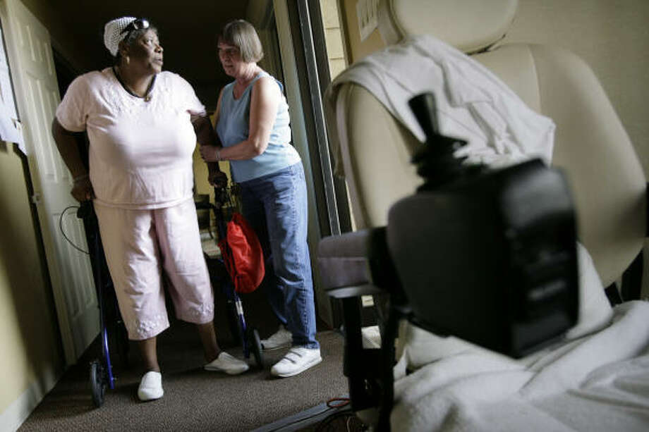 Dorietta Jones, left, gets help up after she waited in line to have her cell phone charged on the one available power strip  at the Braesridge Senior Complex. Photo: Eric Kayne, Chronicle