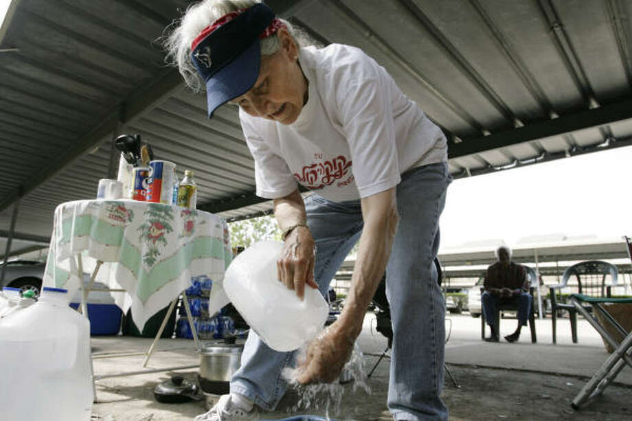 Sylvia June washes her hands under a carport at the Braesridge Senior Complex Wednesday in Houston. June started cooking for a neighbor a few days ago but started cooking for many others in the complex as word spread of her good works. Photo: Eric Kayne, Chronicle