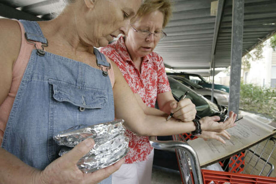 Sheryl Knotts, left, and Terry Kreid get ready to deliver meals to their neighbors at Braesridge Senior Complex. The meals were cooked by Sylvia June under a carport. Photo: Eric Kayne, Chronicle
