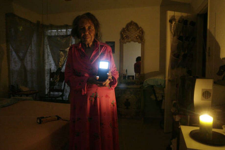 Alma McNack shows the battery-powered television set her son gave her in her room at the Braesridge Senior Complex. When the sun goes down, the complex becomes dark and most residents go to sleep. Photo: Eric Kayne, Chronicle