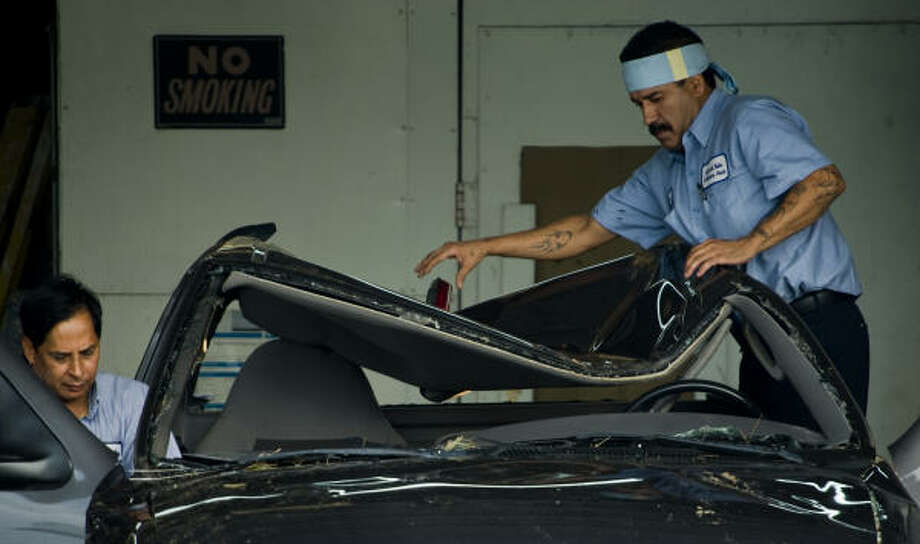Roy Sanchez, left, and Chino Garza begin repairs Wednesday on a pickup truck that had its roof crushed by a tree during Hurricane Ike in Houston. Sanchez said his truck received about $6,000 in damage. Photo: Smiley N. Pool, Chronicle