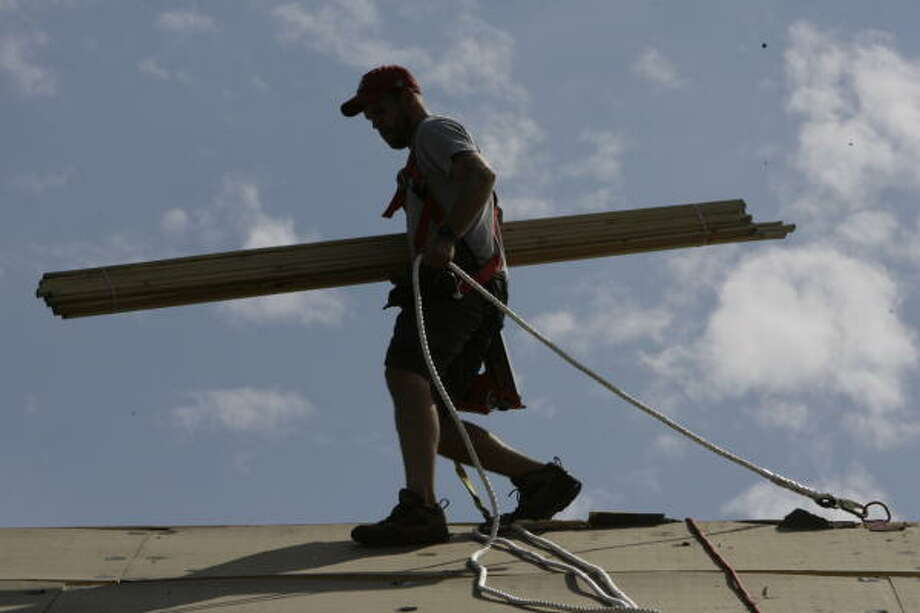 Daniel Jellicorse of Boone, N.C., repairs the roof of First Baptist Church of Alta Loma with other members of the Samaritan's Purse Disaster Relief team who were working in Santa Fe on Wednesday. Photo: Julio Cortez, Chronicle