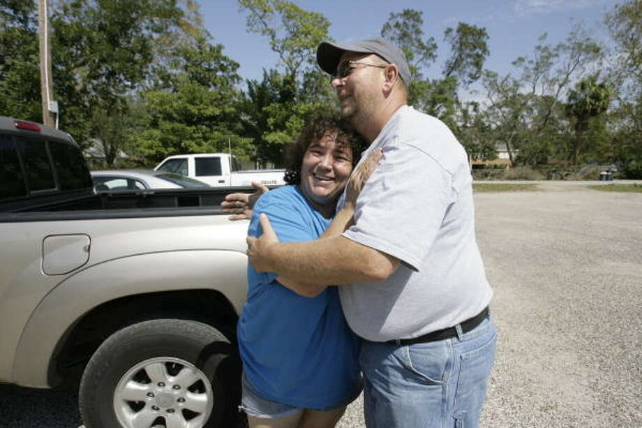Alvin resident Vanessa Haak hugs Samaritan's Purse Disaster Relief volunteer Rick Goodman, of North Carolina, after she was given a plastic tarp to cover the holes Hurricane Ike left in her roof in Santa Fe. Photo: Julio Cortez, Chronicle