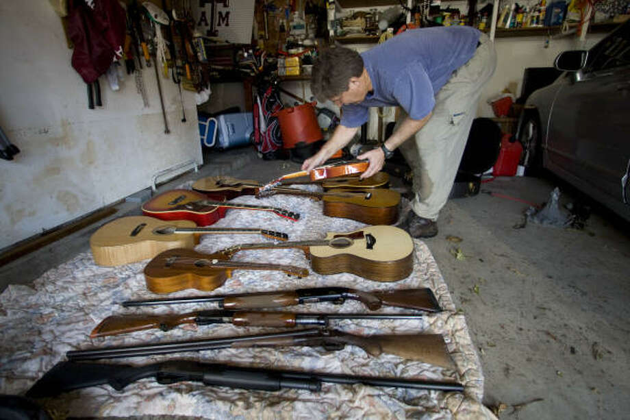 Jim Galbraith sorts through his guitar and gun collections as he attempts to dry them out at his flooded home in Galveston on Wednesday. Photo: Brett Coomer, Chronicle