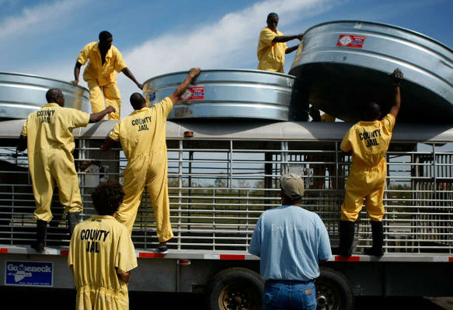 Inmates from the Jefferson County Jail load metal troughs onto a trailer to be filled with fresh water for livestock Wednesday. Pastures are filled brackish floodwaters from the storm surge of Hurricane Ike. Photo: Mark Wilson, Getty Images