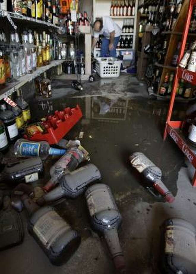 Wayne DeVillier salvages bottles of liquor at the Hitchin' Post Package store in Bridge City Wednesdsay. The store took on 4 feet of water during Hurricane Ike. Photo: Eric Gay, AP