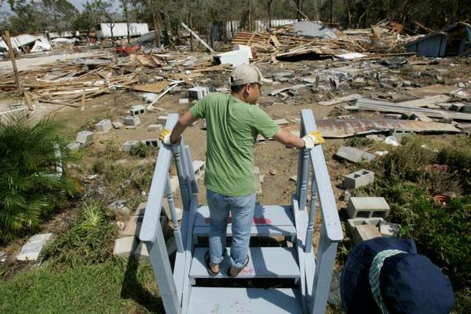 Leon Truong looks over the remains of his mother's ravaged home, where only a staircase is left standing in Oak Island Wednesday. Photo: Marcio Jose Sanchez, AP