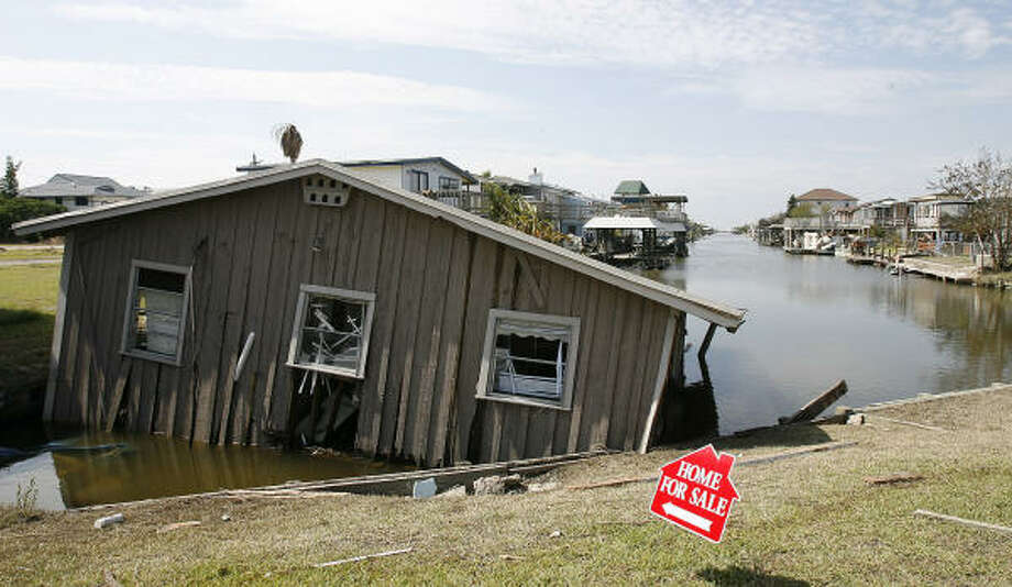A Bayou Vista home rests in a canal between Lakeside and Bayou Vista Drive Wednesday. Photo: Kevin M. Cox, AP / The Galveston County Daily News