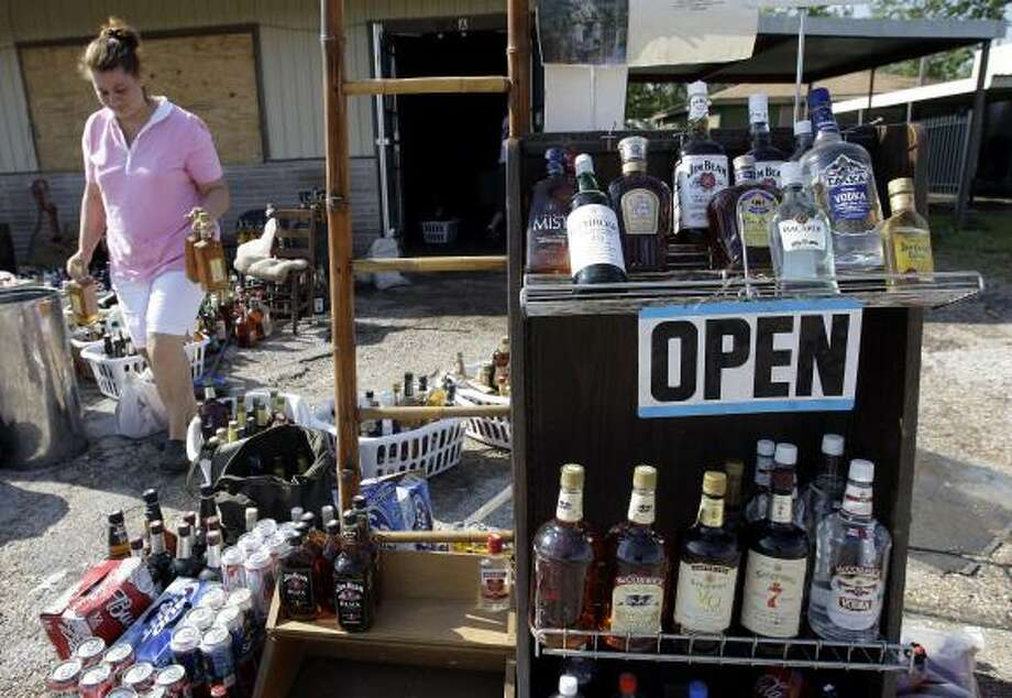 Kim Titus carries bottles of liquor as she helps clean up the Hitchin' Post Package store, co-owned by her mother, in Bridge City on Sept. 17. Photo: Eric Gay, Associated Press