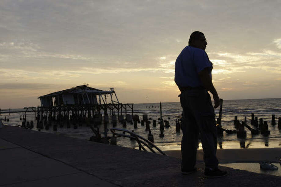 Michael Segura surveys hurricane damage along Galveston's seawall Wednesday. Photo: Matt Rourke, AP