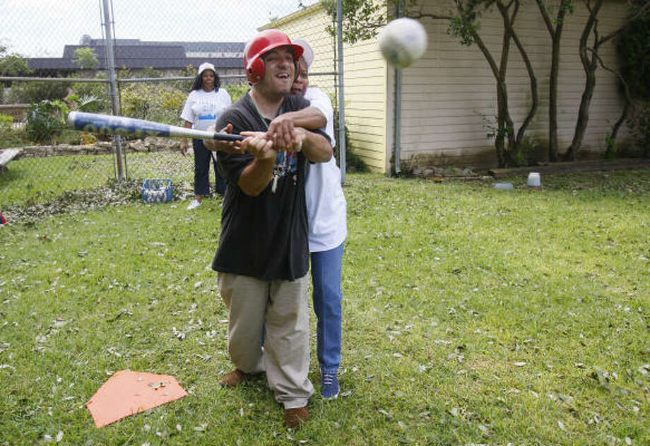 Debrah Smith helps Daniel Rangel with his swing during a baseball game at The Center Serving People with Mental Retardation. Games normally take place on weekends, but nice weather and the power outage got residents outside on Tuesday. Photo: Mayra Beltran, Chronicle