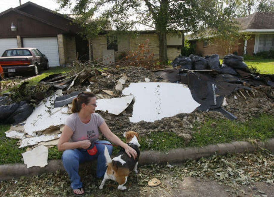 Karen Willard sits in front of her home Tuesday. Her family prepared for Ike, but during the storm their house began crashing down around them. Now they're cleaning out debris and living in an RV. Photo: Mayra Beltran, Chronicle