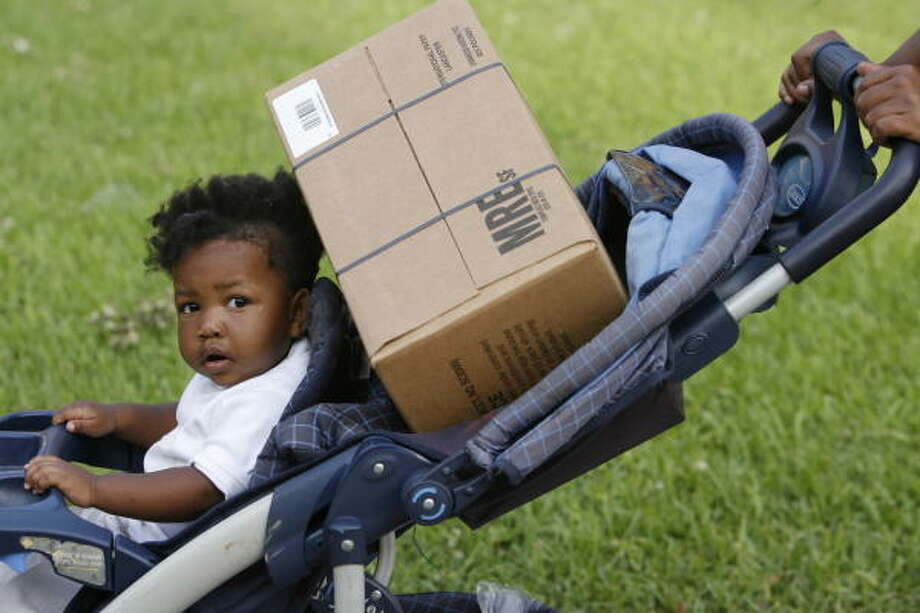 Chrishae Fennix shares her stroller with a box of MREs that her mother picked up from a FEMA POD at Texas Southern University. Third Ward residents were getting supplies there Tuesday. Photo: Billy Smith II, Chronicle