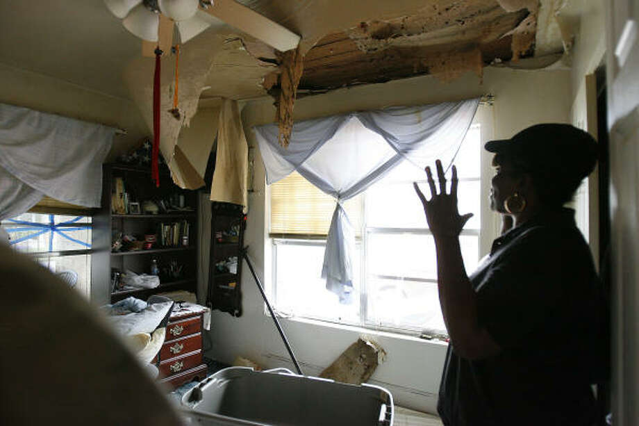 Darlene Davis stands in her mother's home in the 5th Ward Tuesday as she surveys the ceiling damage done by Hurricane Ike. Photo: Karen Warren, Chronicle