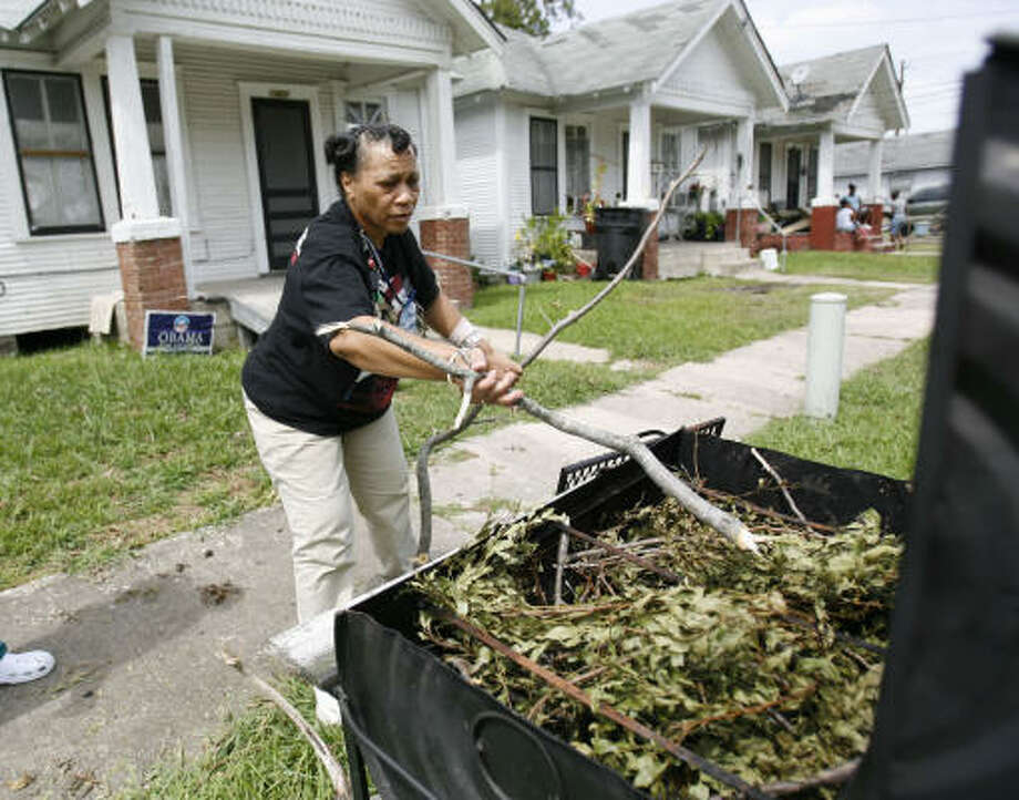 Anopawuia Spinks puts a fallen tree branch on the grill in front of her home in the 5th Ward as she prepares to cook for herself and several of her elderly neighbors Tuesday. Photo: Karen Warren, Chronicle
