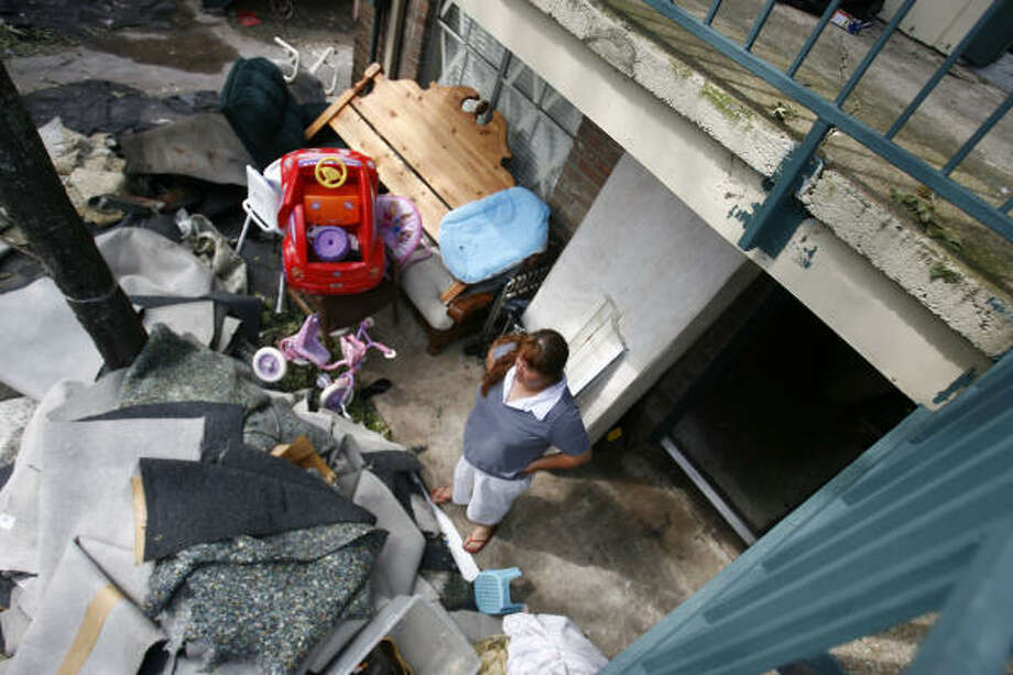 Maria Suarez looks at piles of carpet and destroyed belongings in front of her unit at the Casa Real apartments at Little York Tuesday. Photo: Sharon Steinmann, Chronicle