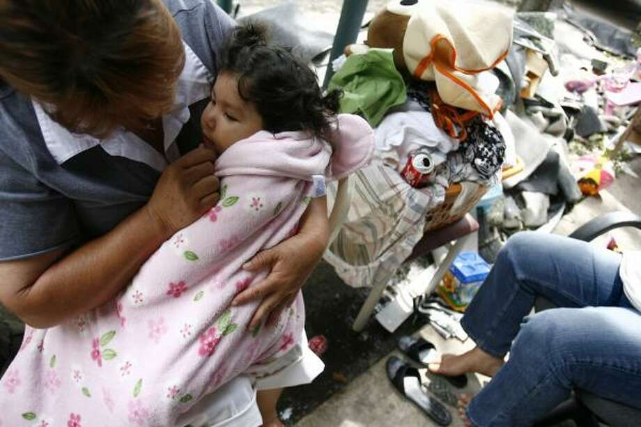 Maria Suarez comforts her niece Rosalinda Galvan, 1, at the Casa Real apartments in Houston where residents were struggling Tuesday to clean out their waterlogged apartments. Photo: Sharon Steinmann, Chronicle