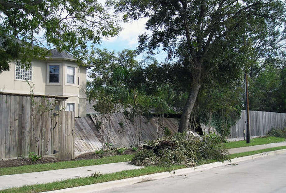 A portion of a fence sits damaged along Avenue B in Bellaire. Photo: Luis Perez, Chronicle