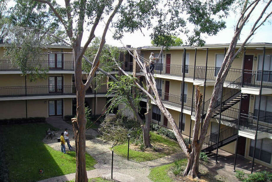 Workers cut down and clear trees damaged and destroyed by Hurricane Ike in an apartment courtyard near Holcombe and Brompton streets in Houston. Photo: Luis Perez, Chronicle