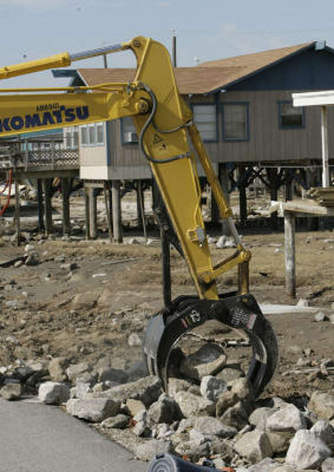 A machine operated by Robert Lopez picks up heavy rocks that were washed away from the beach onto the front yards of Surfside Beach. Photo: Julio Cortez, Chronicle
