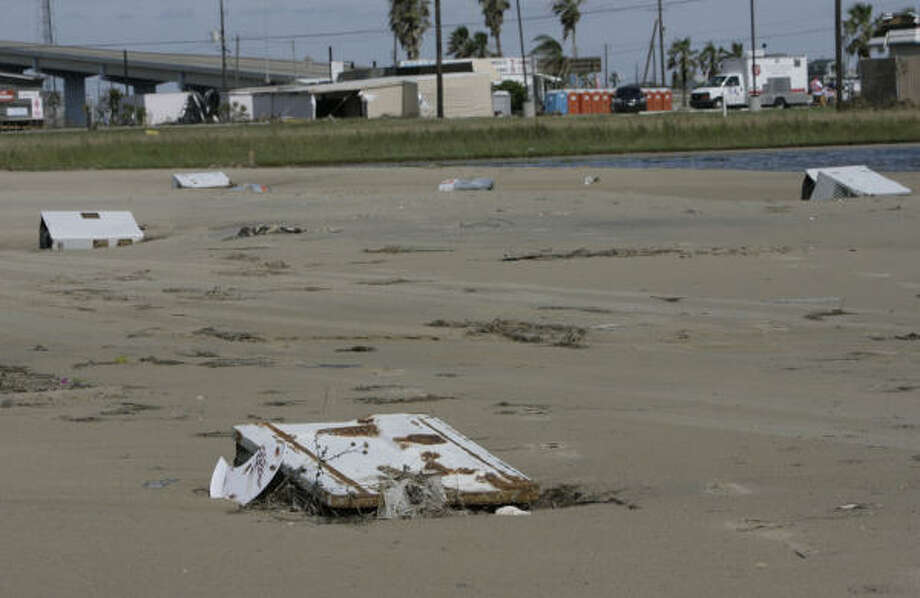 Five air-conditioning units are buried in sand Tuesday after being washed up at Surfside Beach. Photo: Julio Cortez, Chronicle