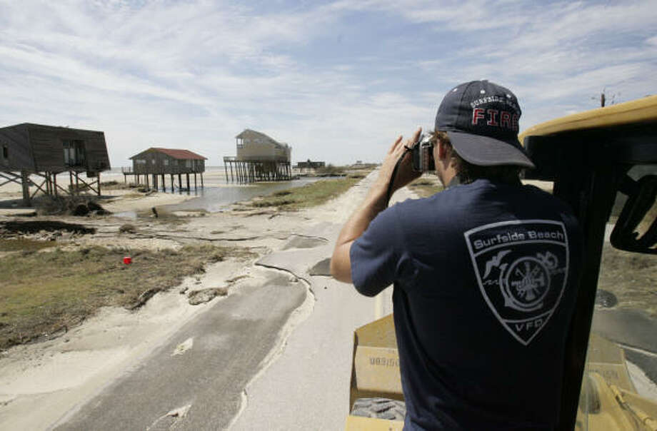 Adam DeVaney, a member of the Surfside Beach Volunteer Fire Department, takes photographs from a trailer to upload to his Web page, where he is helping residents get updates on their houses. The road conditions kept him from reaching Tuesday's destination in Treasure Island, however. Photo: Julio Cortez, Chronicle
