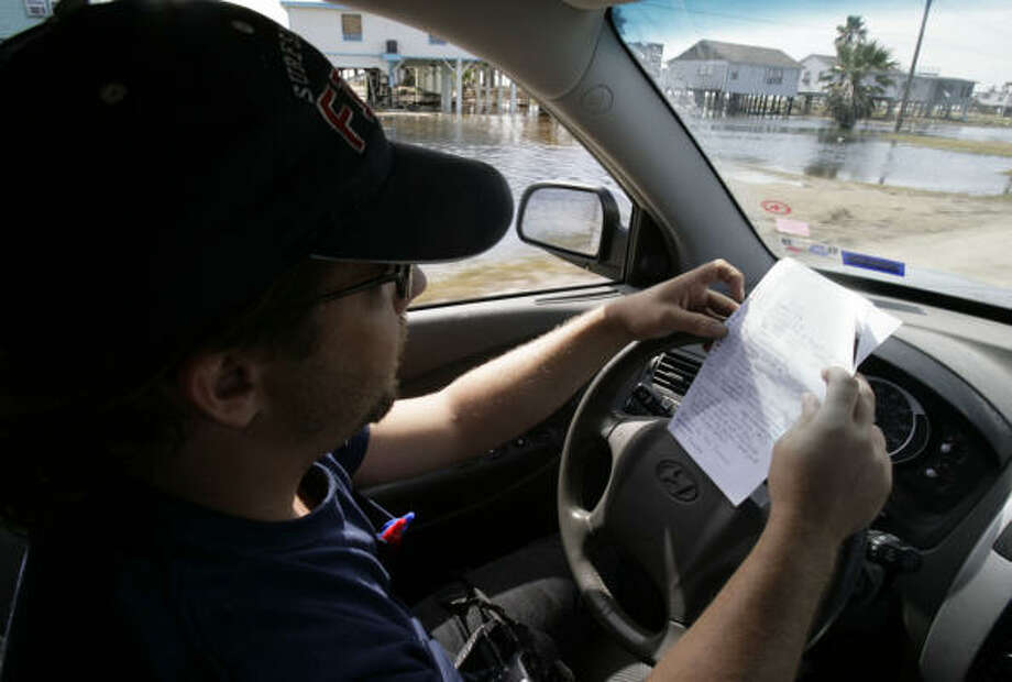 Adam DeVaney checks a list of houses he was requested to photograph and upload to his flickr page. Photo: Julio Cortez, Chronicle