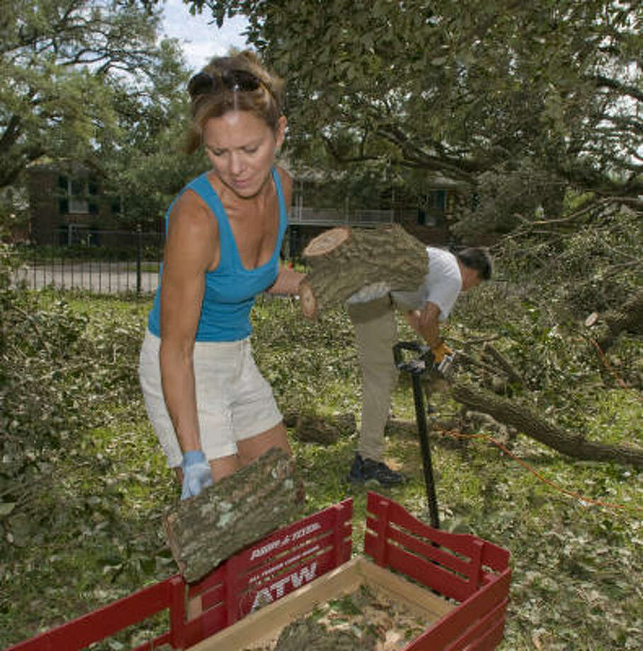 Kim Thompson pitches in at the Fay School on North Post Oak Lane Tuesday to clear away branches, trees and debris. Parents such as Thompson worked side by side with school staff. Photo: Steve Ueckert, Chronicle