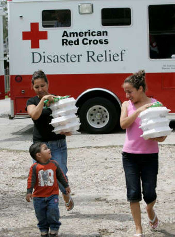 From left, Martha Perez, her son 20-month old son, Emmanuel Matias, and friend Mayra Perez head home after receiving hot meals from the Red Cross. Photo: Marcio Jose Sanchez, AP