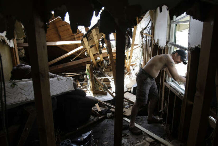 Chad Lavergne searches through his home in Bridge City. Photo: Eric Gay, AP